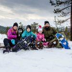Familj ute på snöskovandring